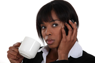 Woman drinking a cup of tea while talking on the phone