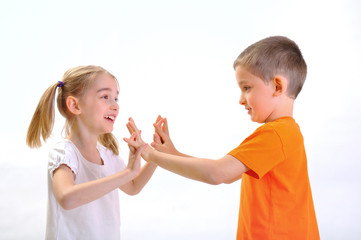 Boy and girl pushing with hands, isolated on white