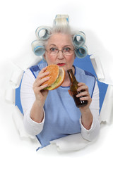 Elderly woman eating a hamburger and drinking beer