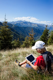 Boy sitting in a mountain meadow using a tablet computer