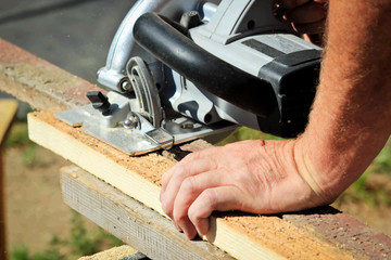 Man sawing board