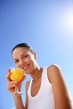 Cheerful woman drinking orange juice