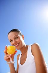 Cheerful woman drinking orange juice