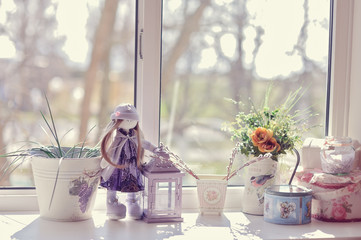 against the window of flowers in pots on the windowsill is a dol