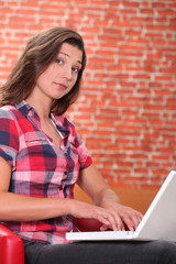Woman using laptop with expression of astonishment