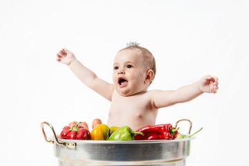 Bambina che ride dentro una pentola con gli ortaggi