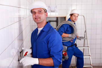 two skilled tradesman working in a empty room