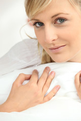 Young woman hugging a white pillow