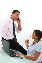 Businessman on the phone and businesswoman sitting at a desk