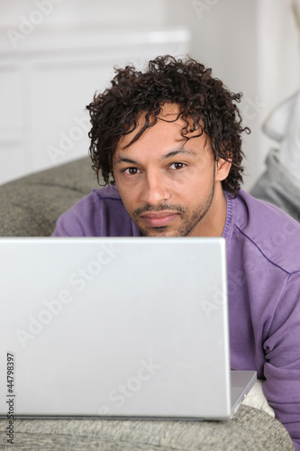 half-caste man with laptop in flat