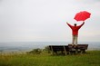 Man with red umbrella is happy in an autumnal landscape