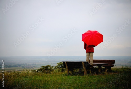Lonesome man with red umbrella at a rainy day