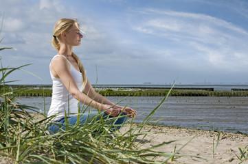 Frau meditierend am Strand
