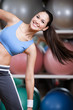 Sportswoman training with dumbbells in gym developing muscles