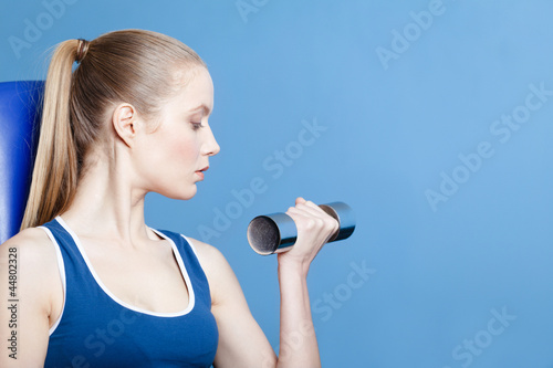 Athlete woman works out with dumbbells in fitness gym