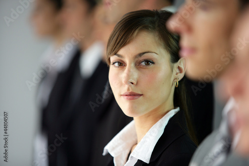 Young woman standing in line with co-workers