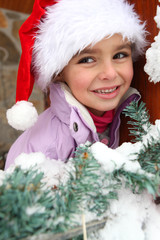 Little girl in Santa hat stood by tree