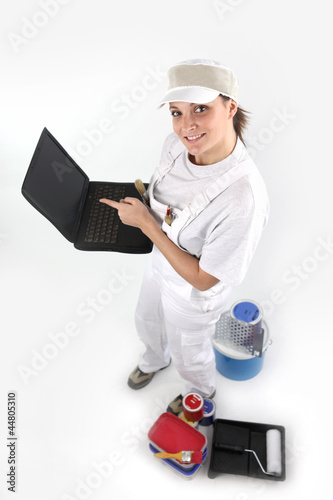 Female painter holding laptop