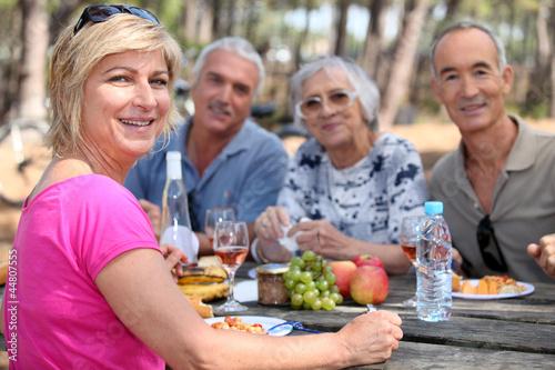 Leinwanddruck Bild Mature friends eating alfresco