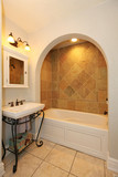 Tub with arch and stone tiles and sink bathroom design.