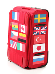 red suitcase with many stickers with flags of different