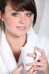Woman in a bathrobe with a hot drink