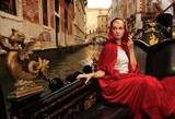 Beautiful woman in red cloak riding on gandola poster