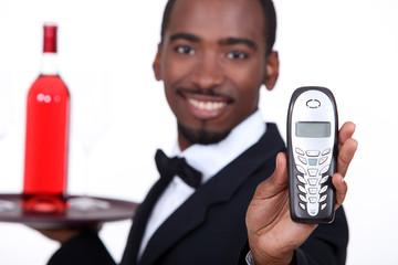 Restaurant waiter holding telephone