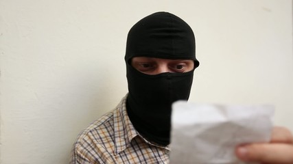 Man with Black Balaclava Reads Paper