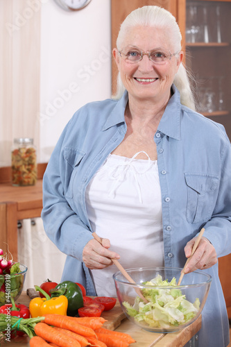 Elderly lady making a salad