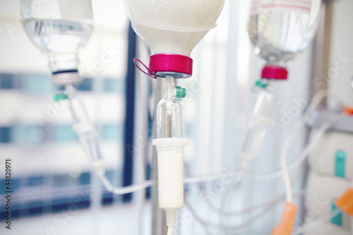 bottle with white drug and intravenous drip system in in hospita