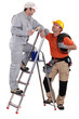 craftsman painter on a ladder speaking with a colleague