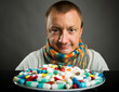 Man looking on plate full of pills