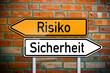 Wegweiser auf Ziegelsteinwand mit Risiko und Sicherheit
