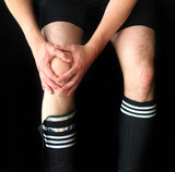soccer male player holding injured knee