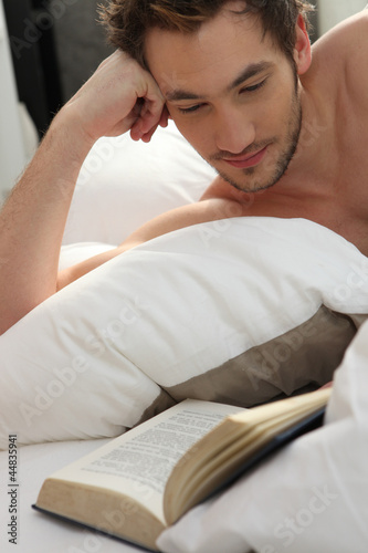 young man bare-chested reading in bed