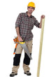 Tradesman with a saw and a wooden plank