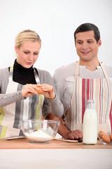 a woman and a boy making a cake