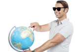 Handsome guy in goggles pointing at globe