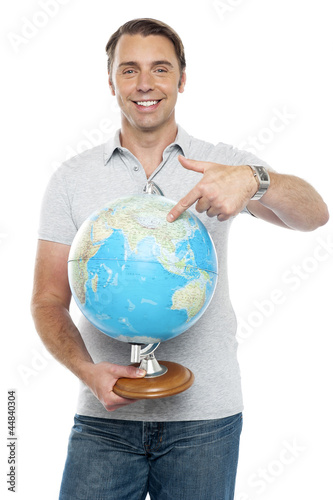 Isolated young man pointing at globe