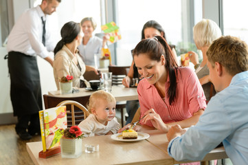 Couple feeding their child cake at cafe