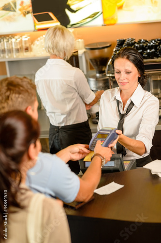 Man paying bill at cafe using card