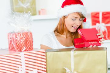 junge frau packt weihnachtsgeschenke aus