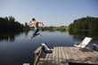 Young man jumping in lake from pier