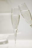 Two full champagne flutes in toast