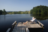 Young businessman sitting on pier at lake relaxing