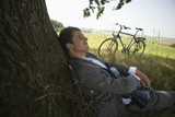 Young businessman leaning on tree near bicycle