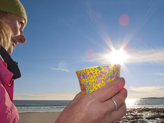 Woman drinking coffee on beach, Gerrans Bay, Cornwall, United Kingdom