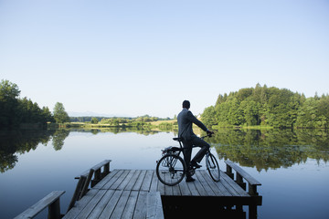 Young businessman with bicycle on pier at lake