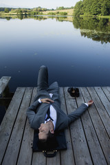 Young businessman relaxing on pier near lake